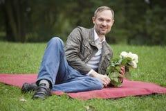 Mens met bloemen in park royalty-vrije stock fotografie