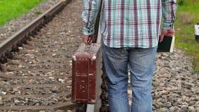 Mens met boek en koffer op spoorweg stock videobeelden