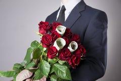 Mens met boeket van rode rozen op een grijze achtergrond Royalty-vrije Stock Afbeeldingen