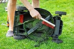 Mens met borstel schoonmakende grasmaaier van oud gras stock foto
