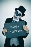 Mens met calaverasmake-up en uithangbord met tekst gelukkige hallowee Royalty-vrije Stock Fotografie