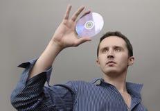 Mens met compact disc Stock Afbeeldingen