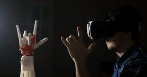 Mens met controles robotachtige hand Innovatieve robotachtige die hand - op 3D printer wordt gemaakt Futuristische Technologie De