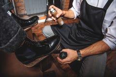 Mens met de nevel van de schortholding voor laarzen royalty-vrije stock afbeeldingen