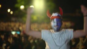 Mens met de schreeuw van het verfgezicht, sprong bij camera in verrukking van overwinningsvoetbal 4k stock footage