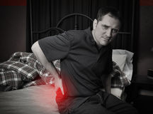 Mens met de Zitting van de Rugpijn op Bed Stock Afbeelding