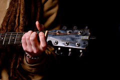 Mens met dreadlocks die gitaar spelen Stock Fotografie