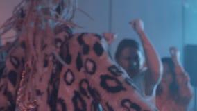 Mens met dreadlocks en luipaardbontjas die omhoog bij gerookte partijruimte dansen stock footage