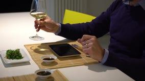 Mens met een baard die chukasalade eten en witte wijn drinken tijdens het diner stock videobeelden