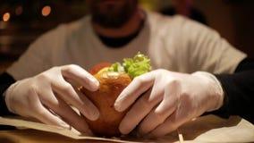 Mens met een baard die een hamburger voorbereidingen treffen te eten cheeseburger