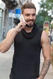 Mens met een baard die met uw slimme telefoon op de straat spreken Stock Foto's