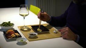 Mens met een baard die sushi eten en witte wijn drinken tijdens het diner stock footage