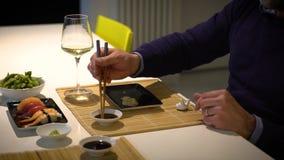 Mens met een baard die sushi eten en witte wijn drinken tijdens het diner stock video