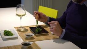 Mens met een baard die sushi eten en witte wijn drinken tijdens het diner stock videobeelden