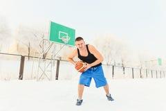 Mens met een basketbal in de winter stock afbeelding
