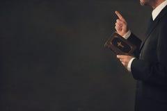 Mens met een Bijbel en een zwiepen metde vinger stock afbeelding
