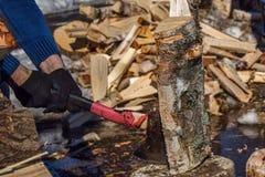 Mens met een bijl hakkend hout in openlucht Royalty-vrije Stock Foto's