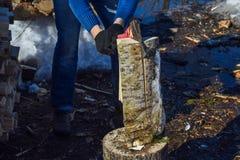 Mens met een bijl hakkend hout in openlucht Stock Afbeelding