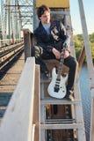 Mens met een elektrische gitaar in het industriële landschap in openlucht Stock Afbeeldingen