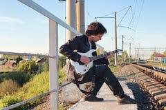 Mens met een elektrische gitaar in het industriële landschap in openlucht Royalty-vrije Stock Afbeeldingen