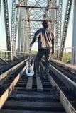 Mens met een elektrische gitaar in het industriële landschap in openlucht Royalty-vrije Stock Afbeelding