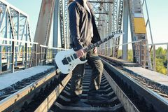Mens met een elektrische gitaar in het industriële landschap in openlucht Stock Foto's