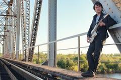 Mens met een elektrische gitaar in het industriële landschap in openlucht Royalty-vrije Stock Foto's