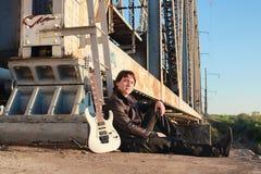 Mens met een elektrische gitaar in het industriële landschap in openlucht Royalty-vrije Stock Foto