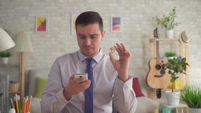 Mens met een gehoorapparaat in zijn hand die informatie over Internet op een smartphone zoeken stock footage