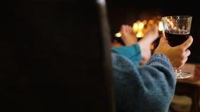 Mens met een glas van wijnzitting door de open haard, warme voeten Comfortabel huis stock videobeelden