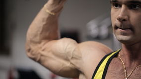 Mens met een intense uitdrukking op zijn gezicht die in de gymnastiek zijn bicepsen en triceps opleiden stock videobeelden