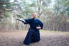 Mens met een Japans zwaard, een katana die Iaido uitoefenen Stock Foto's