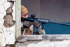 Mens met een kanon in het venster Stock Foto's