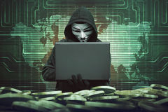 Mens met een kap met anoniem masker die laptop met behulp van aan het binnendringen in een beveiligd computersysteem van bank royalty-vrije stock foto