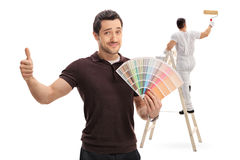 Mens met een kleurenmonster en schilder op ladder Stock Afbeeldingen