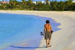 Mens met een metaaldetector op het strand Stock Foto's