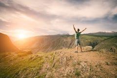 Mens met een rugzak die zich bovenop een berg bevinden royalty-vrije stock foto's