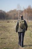 Mens met een rugzak op zijn schouders die op weg in park lopen Royalty-vrije Stock Foto