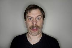 Mens met een snor die een grappig gezicht maken Royalty-vrije Stock Foto's