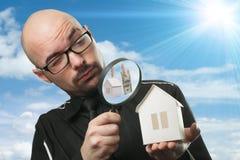 Mens met een vergrootglas en document huis stock afbeelding