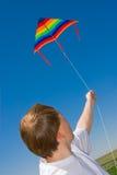 Mens met een vlieger in de hemel Stock Afbeeldingen