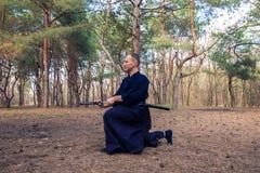 Mens met een zwaard, katana het praktizeren vechtsporten Stock Fotografie