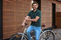 Mens met fiets op straat dichtbij muur royalty-vrije stock afbeelding