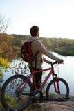 Mens met fietsenrekken dichtbij de rivier Royalty-vrije Stock Afbeeldingen