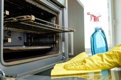 Mens met fles van nevel en vodden schoonmakende oven stock foto