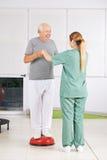 Mens met fysiotherapeut in fysiotherapie stock fotografie