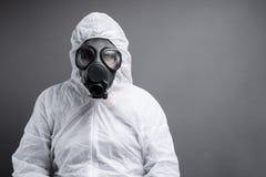 Mens met gasmasker in beschermend algemeen kostuum tegen grijze achtergrond stock afbeelding