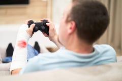 Mens met gebroken wapen in gipsverband met rood bloedspel en holdingscontrolemechanisme voor TV Het concept van de spelverslaving royalty-vrije stock foto