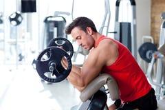 Mens met gewichtheffenapparatuur op sportgymnastiek
