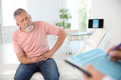 Mens met gezondheidsprobleem bezoekende uroloog stock afbeelding